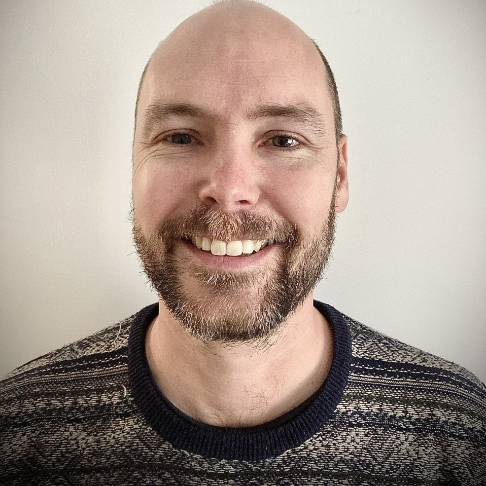 A photo of a QDN staff member Troy Wolski, he is wearing a black and grey patterned shirt and is smiling at the camera.