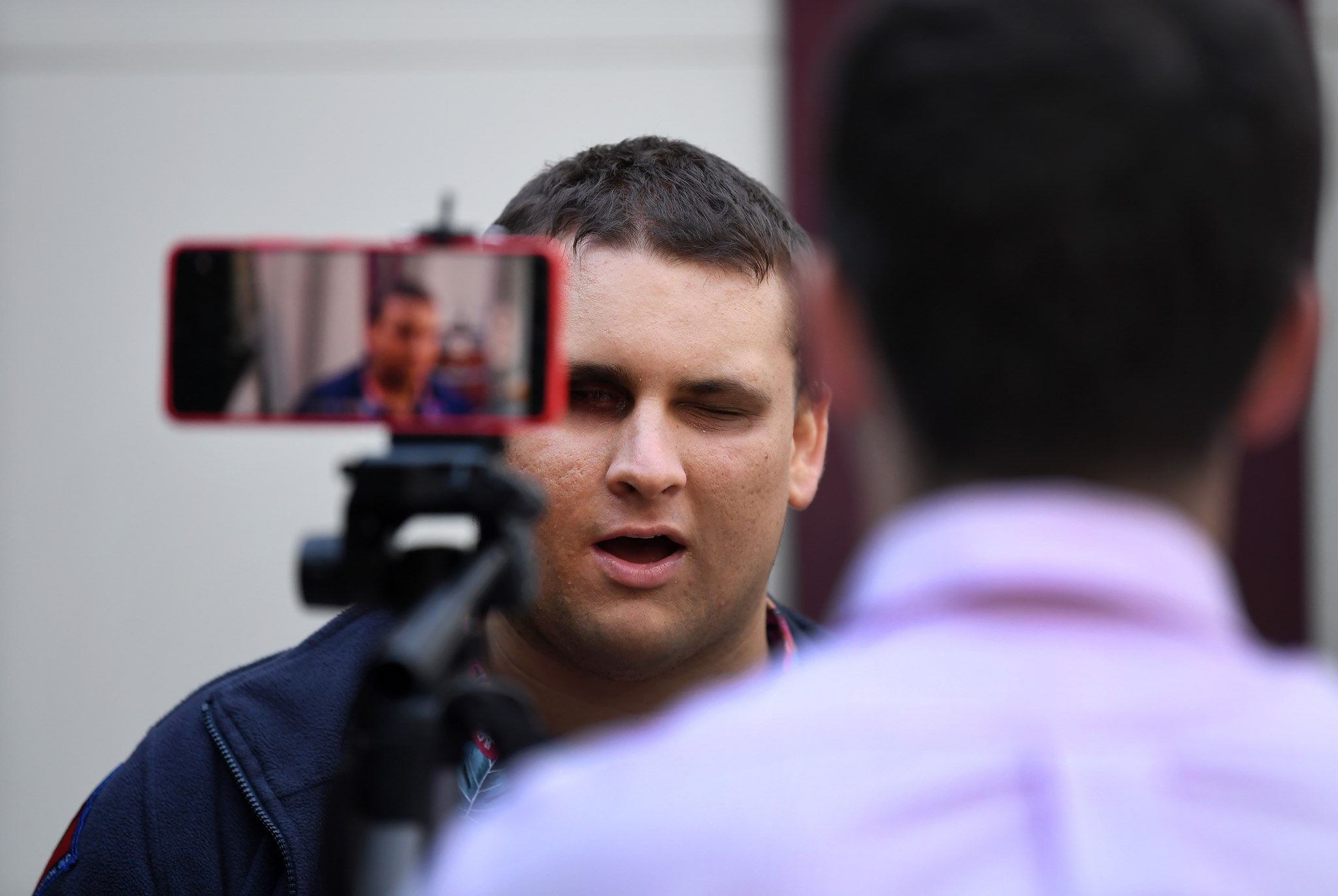 A man with his back to the camera is sitting behind a phone on a tripod. The man and the phone are facing facing a man is being filmed and is looking at the camera.