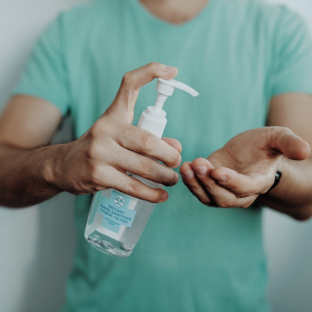 a person in a green shirt, holding sanitiser and about to put some one their hands.