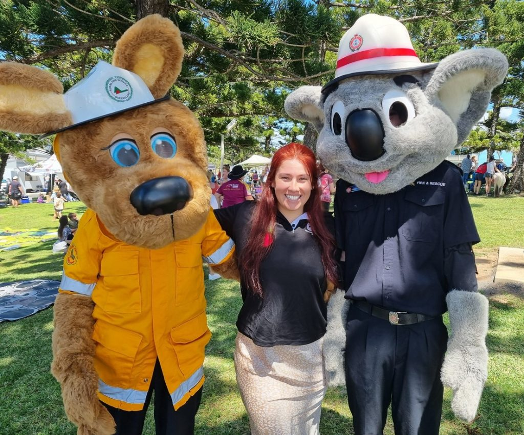 Lisa, a QDN staff member with long red hair and wearing a blue polo, is standing with her arms around two people in large custumes portraying Bushy the Kangaroo, and Blazer the Koala. They are the Queensland Fire and Emergency Services mascots.