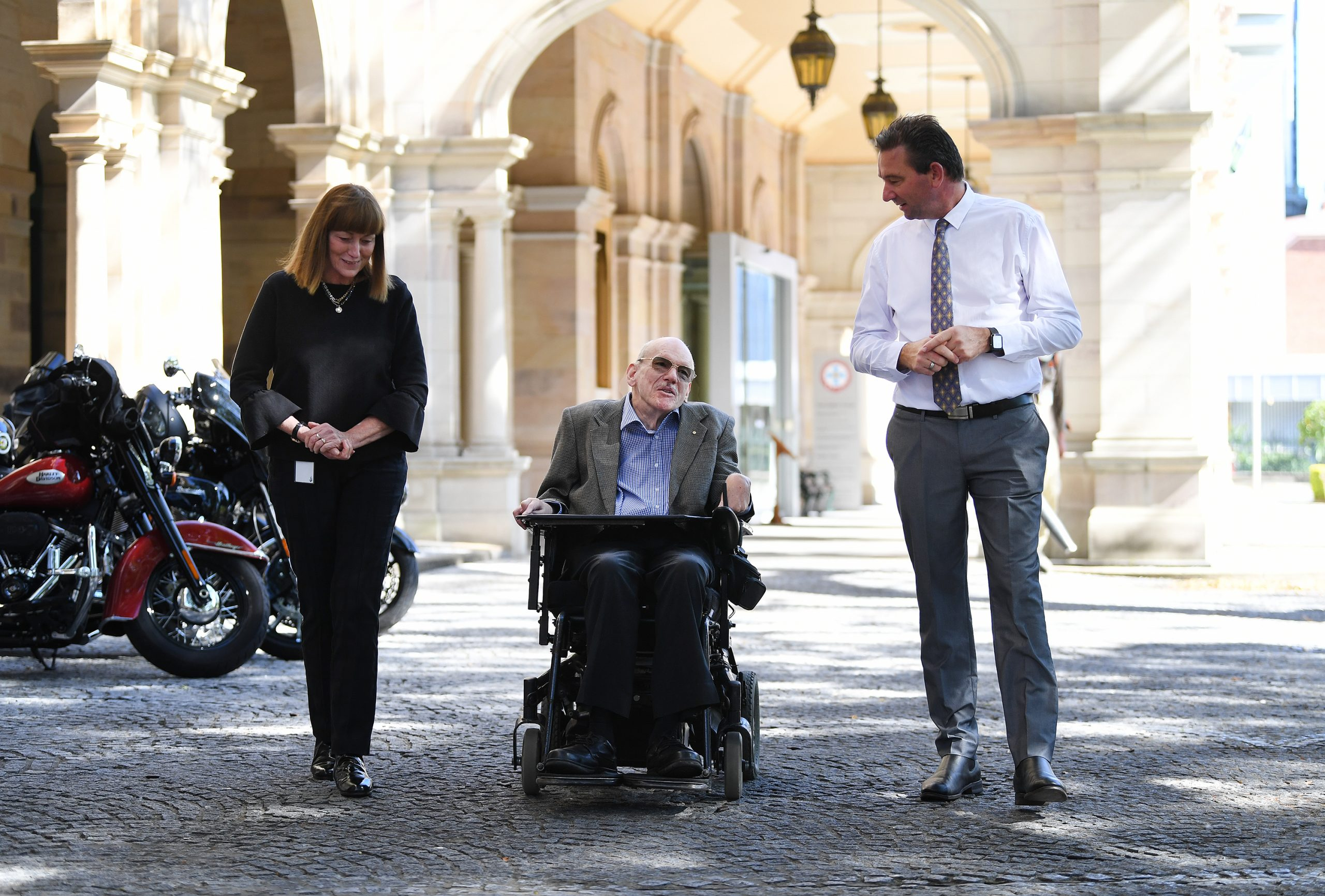 Three people outside walking. There is a lady wearing black, a man in a blazer in a wheelchair and another man on the other side wearing a white shirt and tie.