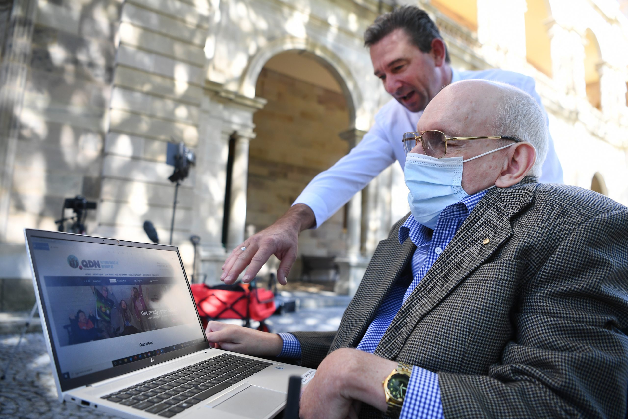 Two men outside. There is a man sitting in a wheelchair. He has a laptop on a table in front of him. Another man is standing and looking over his shoulder, pointing to the laptop screen.
