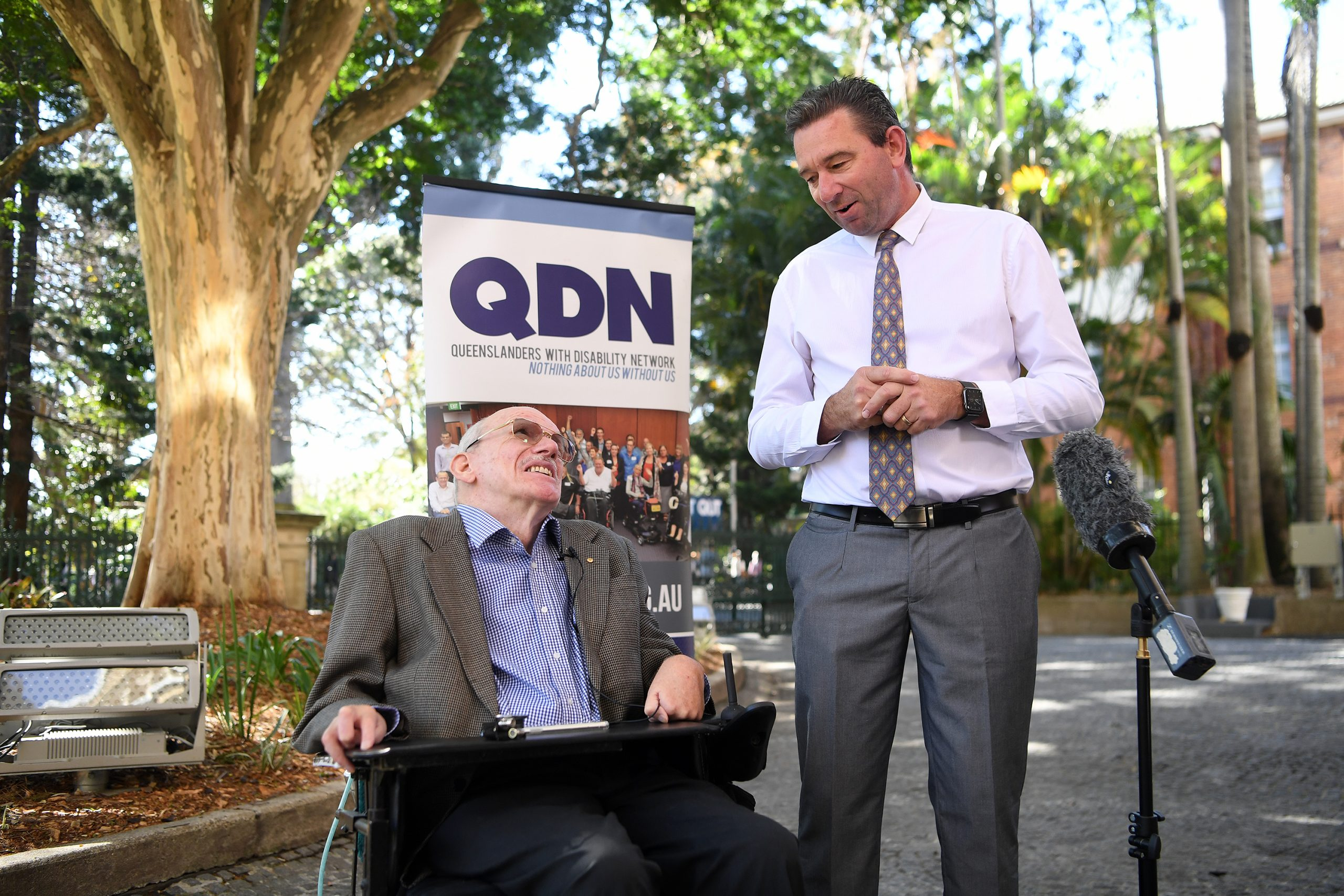 Two men outside under some trees. A man is in a wheelchair looking up at another man who is standing. There is a microphone in the foreground.